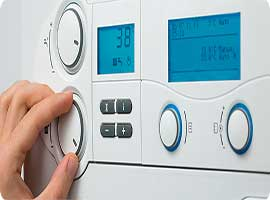 boiler front digital display with a hand turning a dial , heating and plumbers install gas boilers at the best price